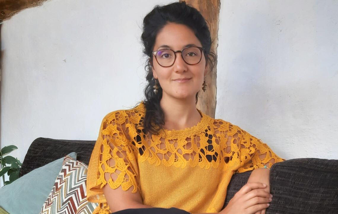 MBSR-Lehrerin Paula Ramirez sitzt auf einem Sitzkissen und schaut in die Kamera: moment by moment 4/2020 Trauma und Transformation