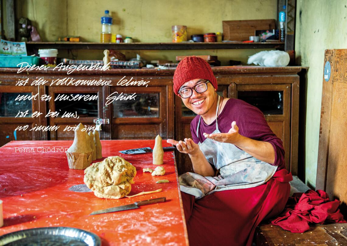 ein tibetischer Mönch lacht fröhlich beim Töpfern