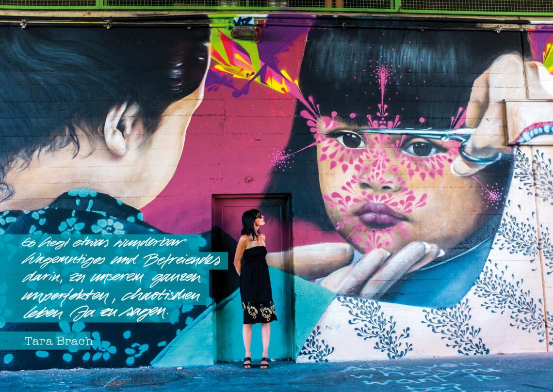 Eine Frau steht vor einer Wand mit grellen Grafittis