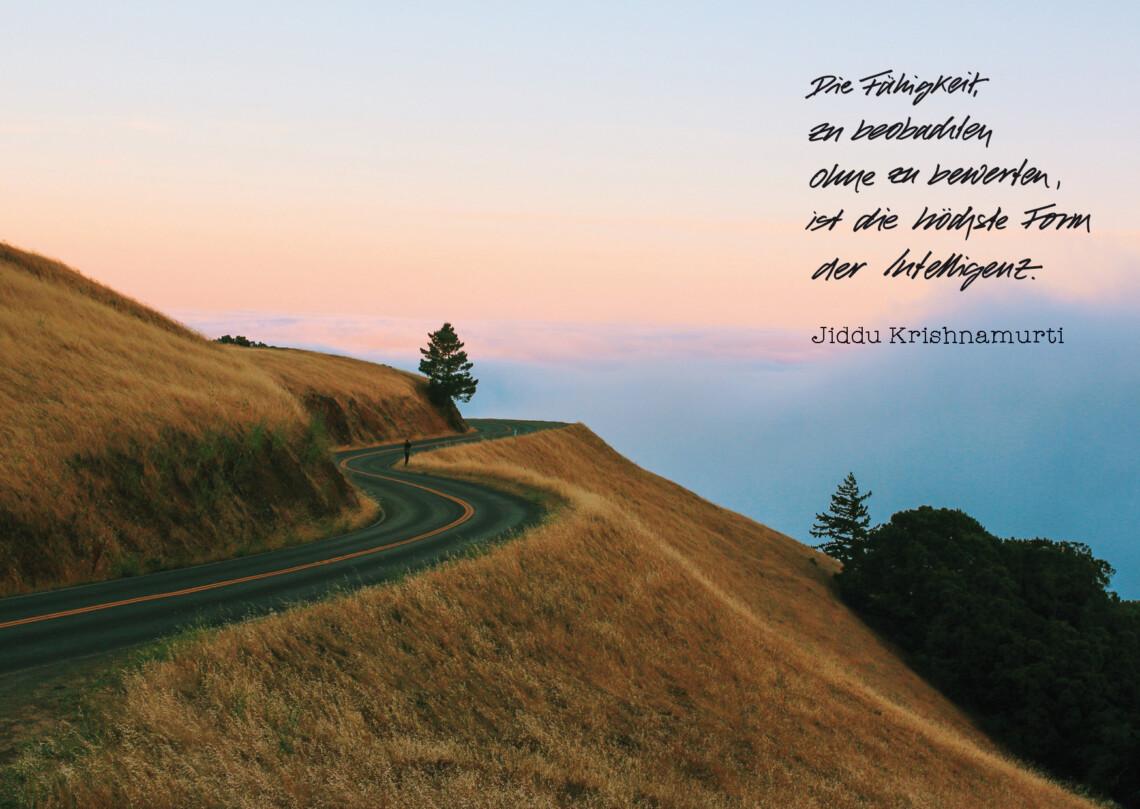 Eine Straße am Berg liegt im bunten Abendlicht