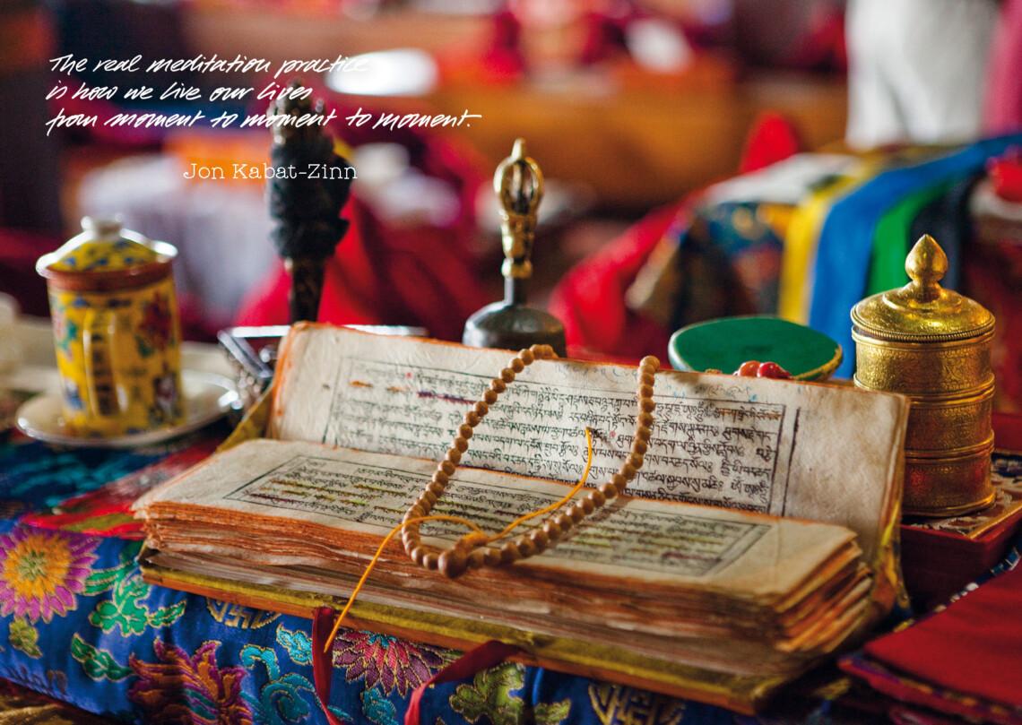eine buddhistischer Text in Sanskrit mit einer Gebetskette und einer Teetasse