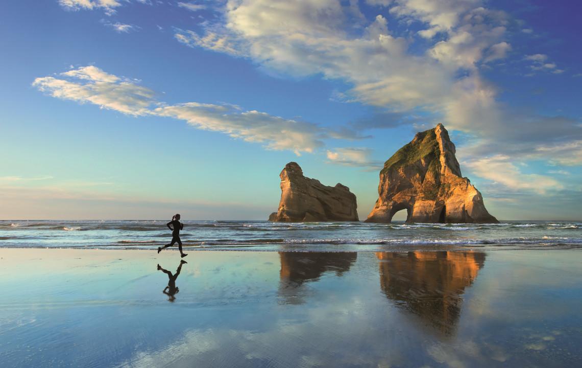 Eine Frau joggt am Strand. Der Morgenhimmel und eine Felsformation im Hintergrund spiegeln sich im Wasser