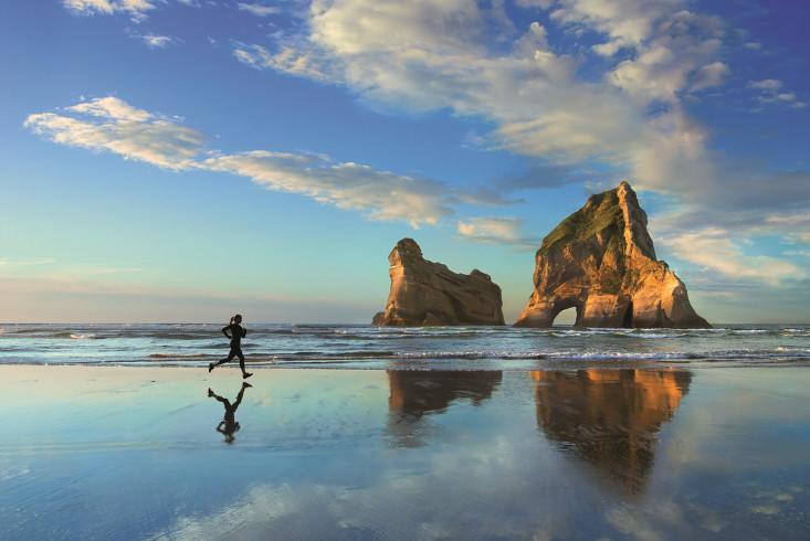 Eine Frau joggt am Strand. Der Morgenhimmel und eine Felsformation im Hintergrund spiegeln sich im Wasser. Link führt zur Leseprobe Ausdauer