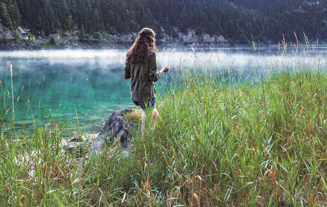 Eine Frau spaziert durch das Schilf am Ufer eines Sees