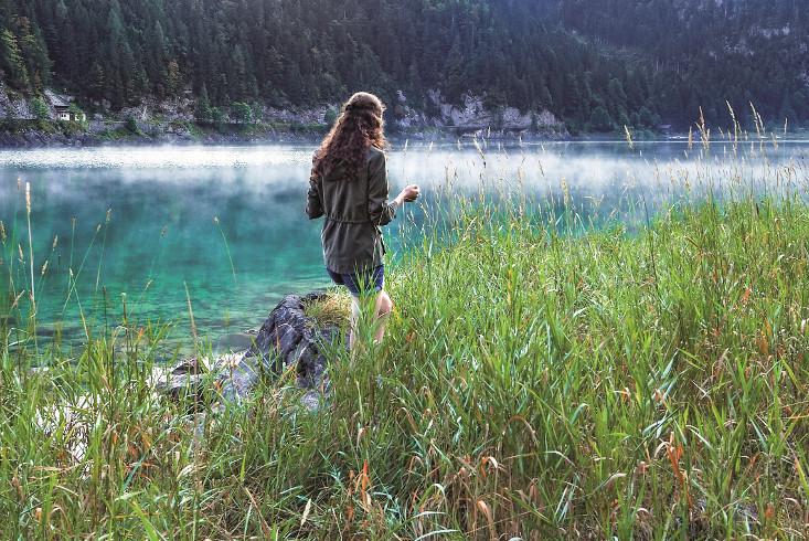 Eine Frau spaziert durch das Schilf am Ufer eines Sees. Link führt zur Leseprobe Never Give Up