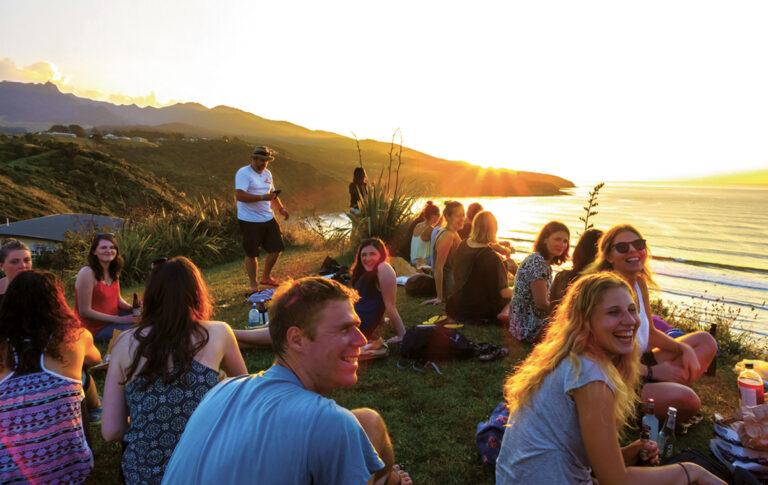 Eine Gruppe junger Leute sitzt entspannt und fröhlich im Gras. Sie befinden sich an einem hügeligen Meeresufer, im Hintergrund geht die Sonne unter.