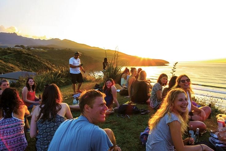 Eine Gruppe junger Leute sitzt entspannt und fröhlich im Gras. Sie befinden sich an einem hügeligen Meeresufer, im Hintergrund geht die Sonne unter. Link führt zur Leseprobe Leben in einer unsicheren Welt.