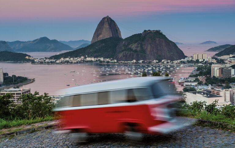 Verschwommene Aufnahme eines roten VW Bulli in voller Fahrt. Im Hintergrund ist der Zuckerhut und der Hafen von Rio de Janeiro zu sehen.
