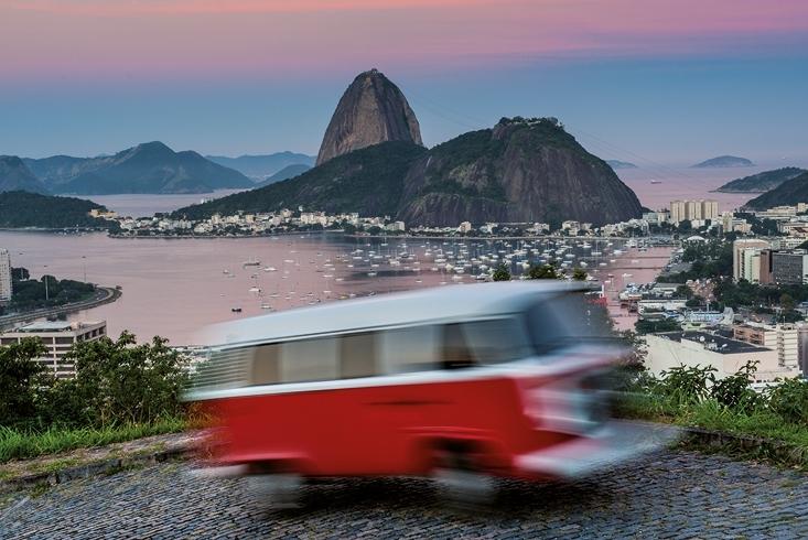 Verschwommene Aufnahme eines roten VW Bulli in voller Fahrt. Im Hintergrund ist der Zuckerhut und der Hafen von Rio de Janeiro zu sehen. Link führt zur Leseprobe Mit dem Bulli um die Welt.