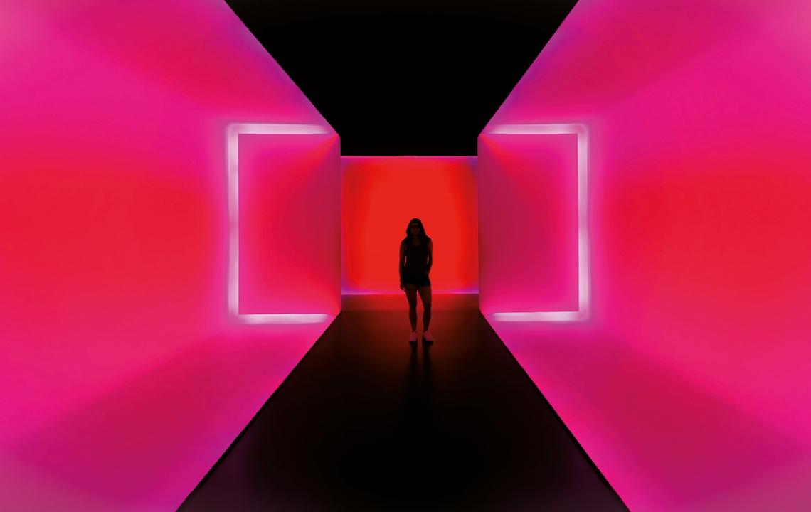 Eine Frau steht in einer Kunstinstallation. Sie ist umgeben von grellen pinken Wänden, lediglich ihre dunkle Silhouette ist erkennbar.