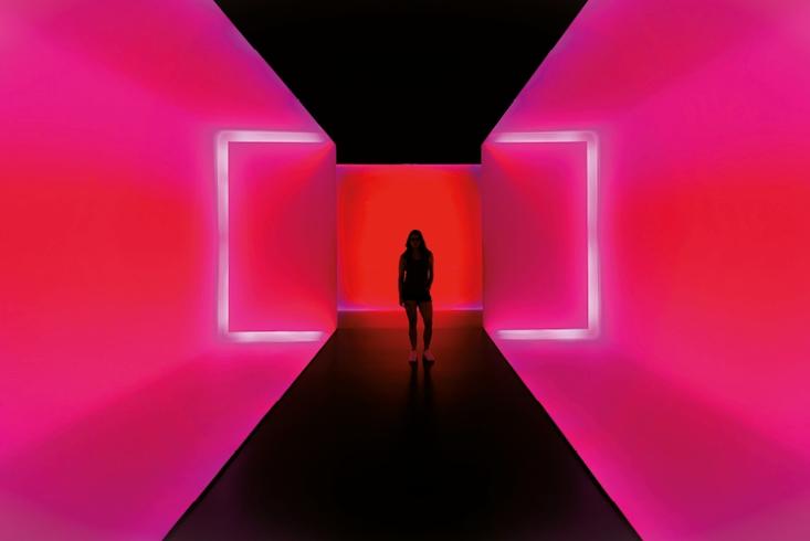 Eine Frau steht in einer Kunstinstallation. Sie ist umgeben von grellen pinken Wänden, lediglich ihre dunkle Silhouette ist erkennbar. Link führt zur Leseprobe Die Psychedelische Reise zu uns selbst.