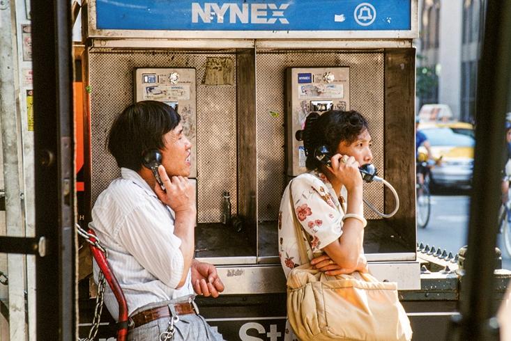 Ein Mann und eine Frau stehen an zwei benachbarten öffentlichen Telefonapparaten und telefonieren. Link führt zur Leseprobe des Artikels Kommunikation im Informationszeitalter von Gert Scobel.
